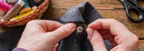 Mani che cuciono un bottone su una camicia su misura a Marano di Napoli