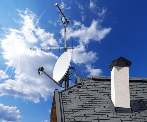 Una parabola e un'antenna su un tetto