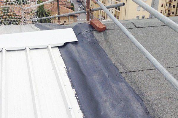 un tetto non ancora ultimato, si vedono travi di ferro una lastra di metallo bianca e un mattone