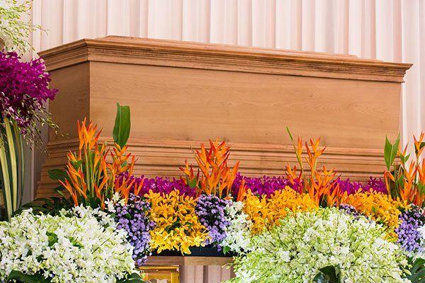 una bara in legno e sotto dei fiori arancioni,bianchi,viola e azzurri