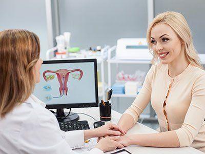 un medico e una donna sedute alla scrivania ch si tengono per mano