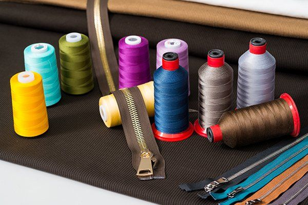 dei fili da cucito  di diversi colori e una cerniera