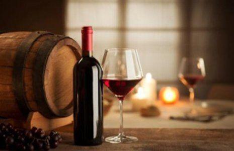 un bicchiere di vino rosso, una bottiglia, dell'uva nera e un barile di legno