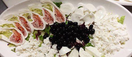 un piatto con dei formaggi molli, mozzarella , uva nera e degli involtini con prosciutto e insalata