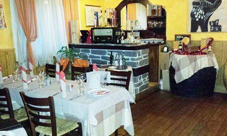 interno del ristorante con vista di un tavolo apparecchiato e del bancone della cassa in mattonelle in pietra