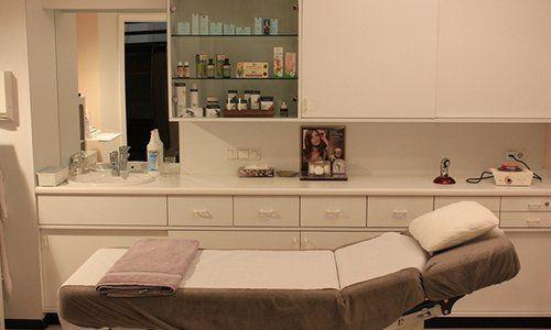 un lettino con un asciugamano piegato e un armadio bianco con dei prodotti
