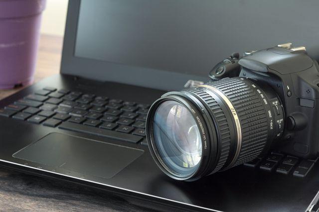 fotocamera nera appoggiata su un computer
