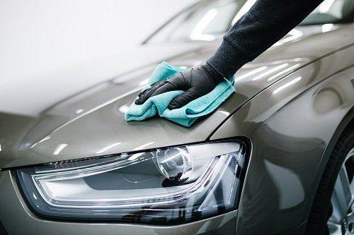 Una mano con guanto  mentre passa  il panno all'automobile per lucidarlo