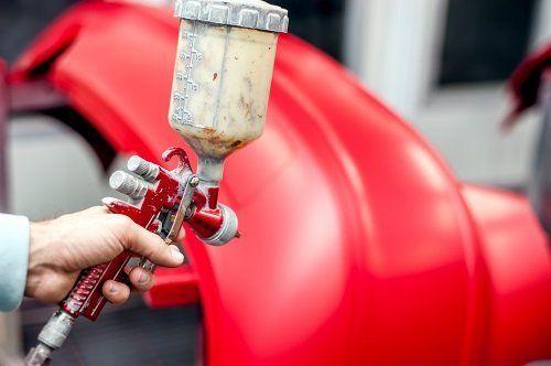 Una mano utilizza la pistola per verniciatura per dipingere un pezzo di auto di colore rosso