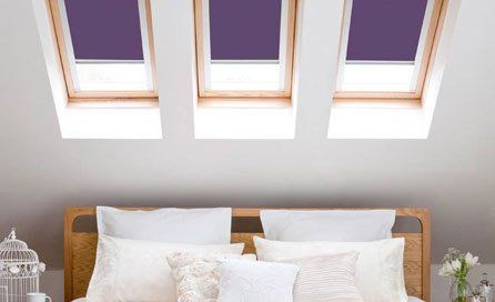 Purple blinds at three skylight windows above a bed with white linen and wooden headboard