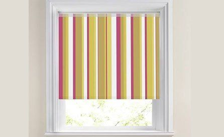 A small window with roller blind in red, lime and white stripes