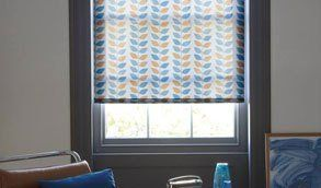 A roller blind patterned with blue and yellow leaf shapes