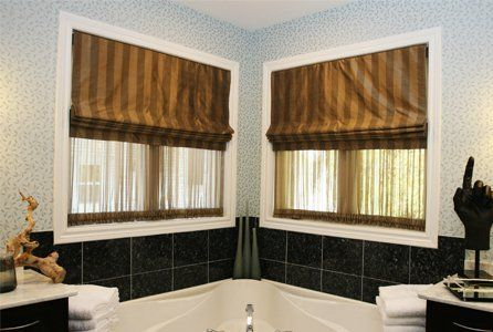 Brown stripe roman blinds in a bathroom with corner bath and black wall tiles