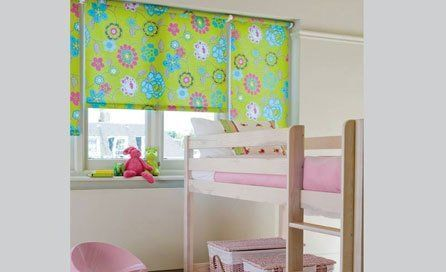 A child's pink bunk bed in front of a window with bright green flowered roller blinds at the window