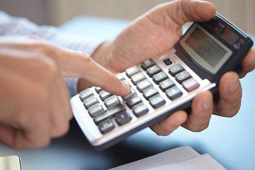 una mano che tiene una calcolatrice e l'altra che digita i tasti