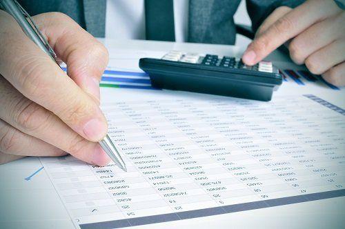 una mano con una penna e l'altra durante l'utilizzo di una calcolatrice