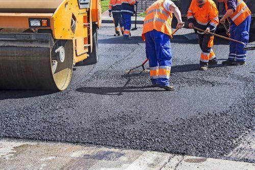 cinque uomini durante lavoro di asfaltatura strada