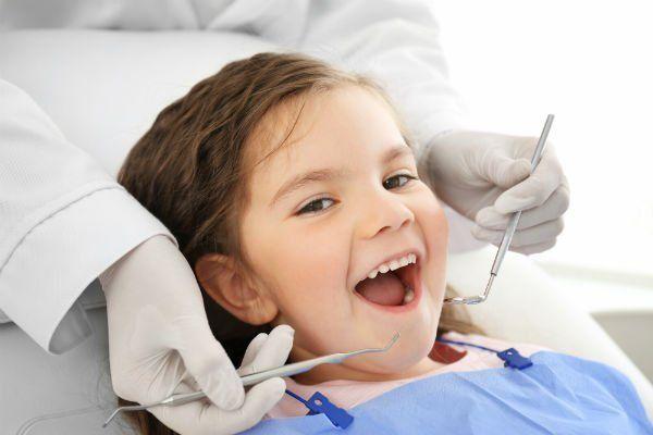 Bambina con la bocca aperta pronta per l'intervento ai denti