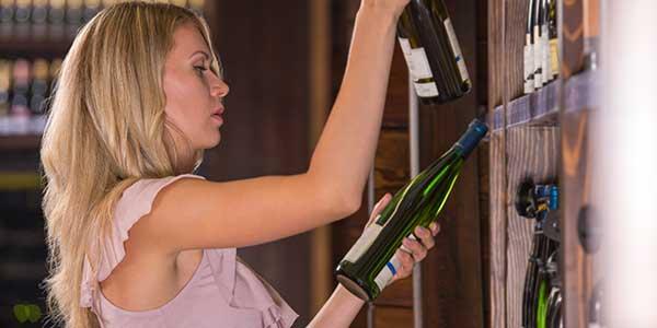 una donna in un supermercato sta scegliendo dei vini bevande a domicilio provincia di Parma