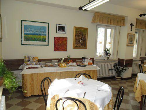 tavoli apparecchiati e un buffet piccolo con cereali, brioches e succhi di frutta