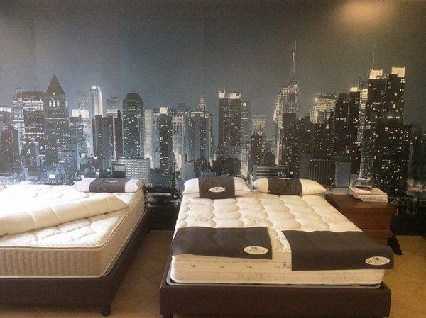 due letti matrimoniali con dei materassi Permaflex e dietro un poster di una città di notte