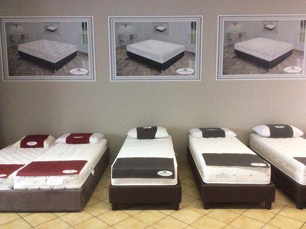 esposizione di materassi su dei letti singoli e sopra 3 cornici con le immagini dei materassi
