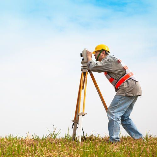 person using land surveying equipment