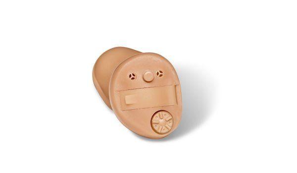 Esposizione di un apparecchio acustico di color beige con un tasto