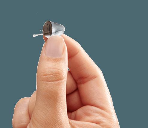 Persona tiene in mano apparecchio acustico