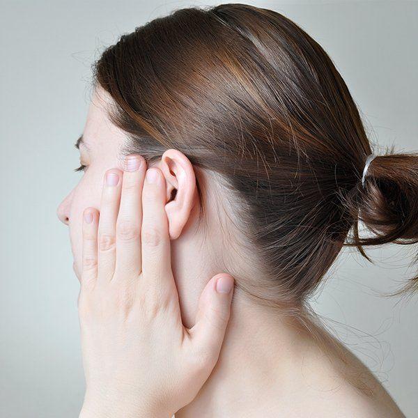 Donna si tocca l'orecchio