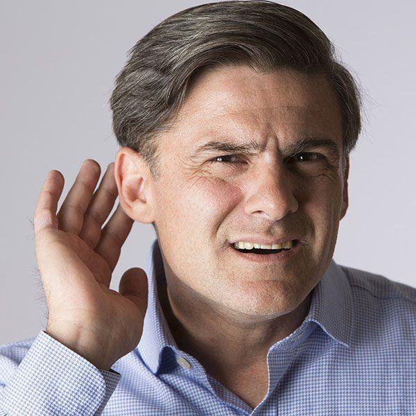 Uomo fa gesto di non sentire con la mano a coppa