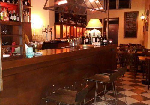 un bancone di un bar e vista di alcuni tavoli