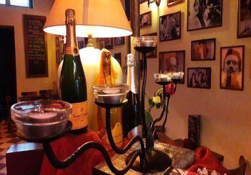 un candelabro con dei lumini e accanto delle bottiglie di spumante