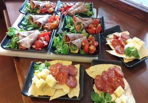 dei vassoi con salumi, formaggi e insalata
