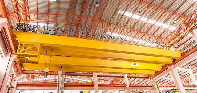 una struttura di ferro gialla e altre arancioni che sorreggono un tetto di un capannone