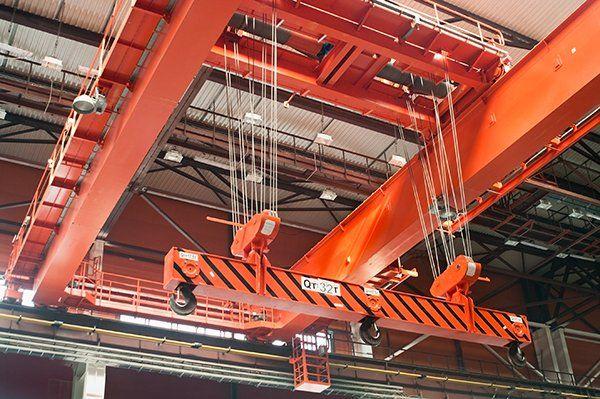 una struttura di ferro arancione con dei cavi e tre ganci