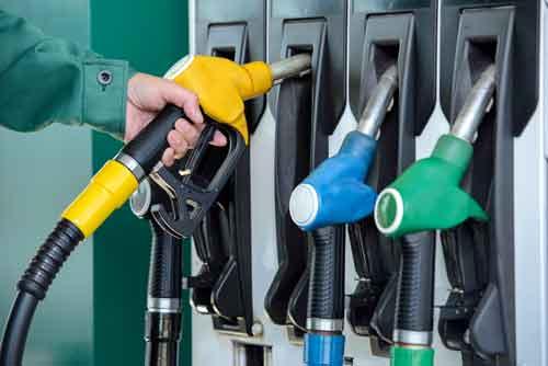 Un benzinaio che ripone la pompa di benzina