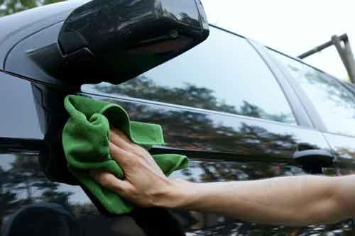 Un uomo che lava una macchina con una pezza verde