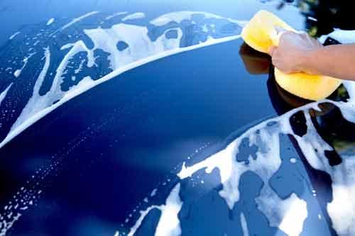 Una persona che lava una macchina blu con una spugna gialla