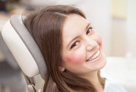 A smiling young lady in the dentist's chair