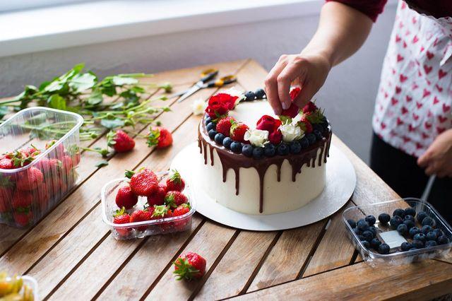 torta con glassa alla vaniglia e al cioccolato e decorazione di frutti di bosco