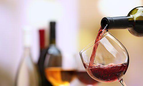 Vino rosso che versa nel bicchiere di vino, primo piano