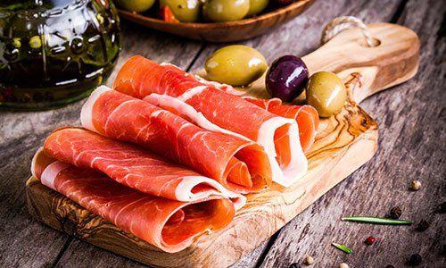 fettine sottili di prosciutto con olive miste sul tagliere di legno