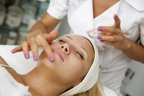 estetista esegue trattamento viso su giovane donna