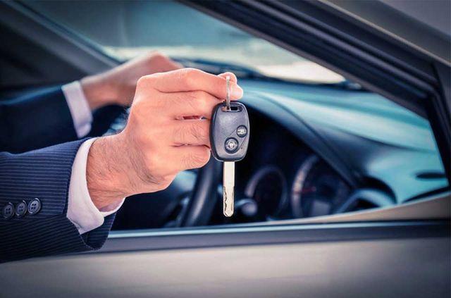 man holding keys out a car window