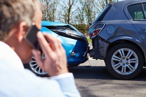un uomo al telefono con due macchine incidentate sullo sfondo