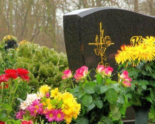 dei fiori colorati vicino a una lapide