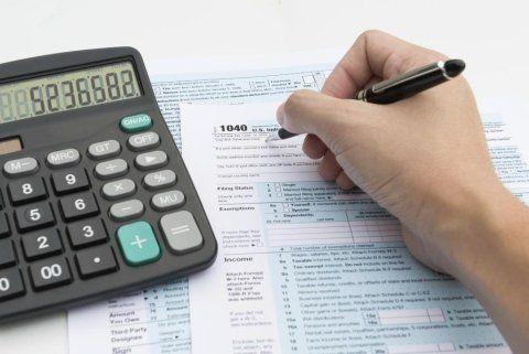 mano con una penna mentre scrive su un foglio e un calcolatrice