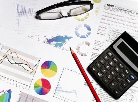 calcolatrice, mattia e occhiali da vista su un foglio finanza