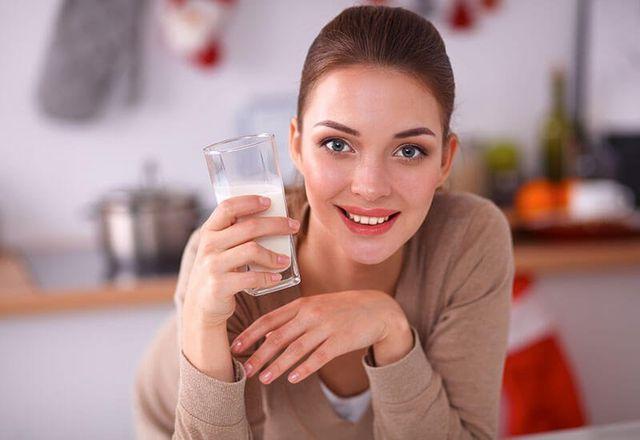 donna con in mano un bicchiere di latte